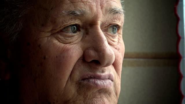 pensive old man near the window: senior, wrinkled, old man, elderly man video