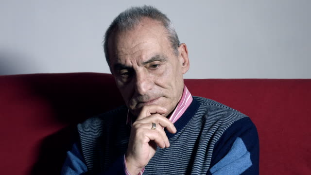 pensive old man opens his eyes and sighs: sofa, home, depression video
