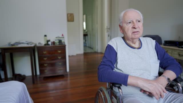 pensive senior man in wheelchair - distrarre lo sguardo video stock e b–roll