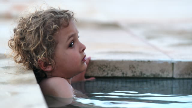 Pensive small boy child inside swimming pool water thinking Pensive small boy child inside swimming pool water thinking one boy only stock videos & royalty-free footage