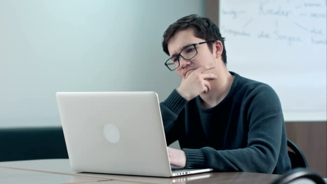 Pensive student with laptop studying in the university library video