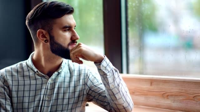 nachdenkliche stilvolle hipster junge mann denken blick auf nasses fenster bei regenwetter mittlere nahaufnahme - introspektion stock-videos und b-roll-filmmaterial