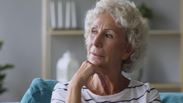 nachdenkliche nachdenkliche seniorin denkt weg sitzend auf sofa - introspektion stock-videos und b-roll-filmmaterial