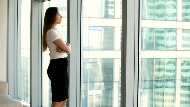 Pensive thoughtful young businesswoman standing near full length office window video