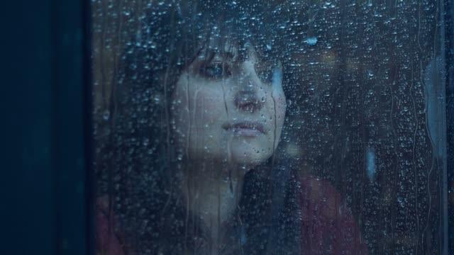 zamyślony kobieta z okna w deszczowy dzień. ujęcie w slowmotion - samotność filmów i materiałów b-roll