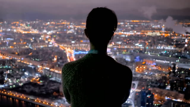 Pensive woman looking at night city from skyscraper Back view: pensive woman silhouette looking at night cityscape. View throw window of skyscraper on street with light bokeh illumination at evening. Success, sightseeing, opportunity and future concept chance stock videos & royalty-free footage