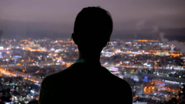 Pensive woman looking at night city from skyscraper Pensive woman silhouette looking at night cityscape. View throw window of skyscraper on street with light bokeh illumination at evening. Success, opportunity and future concept chance stock videos & royalty-free footage