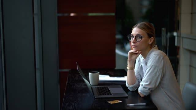 Pensive woman thinking on idea while working remotely on digital netbook connected to wireless internet