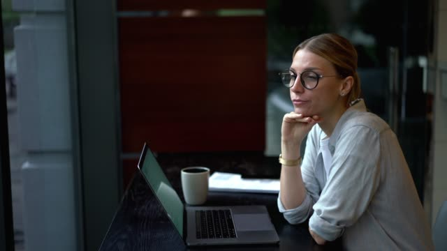 Pensive woman working remotely on digital netbook connected to wireless internet