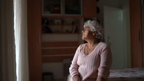 pensive endişeli yaşlı kadın pencereden bakarak ve düşünme - abd dışı yer stok videoları ve detay görüntü çekimi