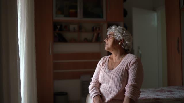 pensive orolig äldre kvinna tittar genom fönstret och tänker - sentimentalitet bildbanksvideor och videomaterial från bakom kulisserna