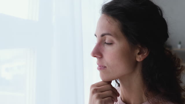 Pensive worried young adult woman looking outside through window