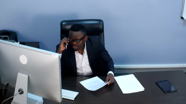 Pensive young afro-american businessman having a phone call, discussing documents and sitting in office video