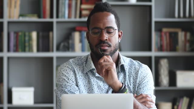 Pensive young biracial man looking at laptop screen.
