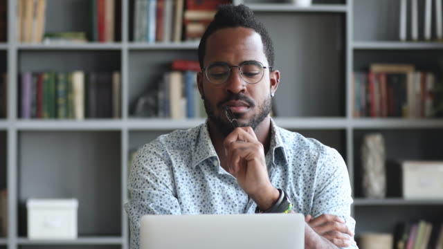 vídeos de stock, filmes e b-roll de jovem jovem e pensativo olhando para a tela do laptop. - contemplação
