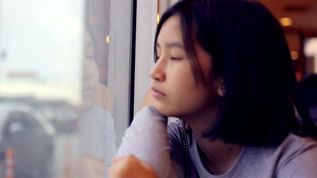 沉思的年輕女孩透過窗戶看 - 看窗外 個影片檔及 b 捲影像
