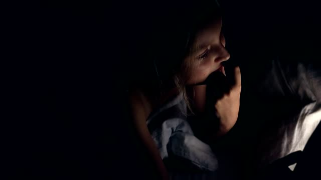 Pensive young girl thinking and touch lips and mouth with hand. Caucasian girl with tablet in bed night. video