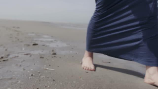 uomo pensieroso giovane donna in una giacca in denim piedi su solitario sulla spiaggia - scalzo video stock e b–roll