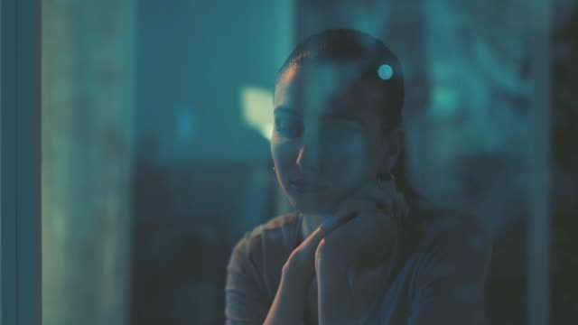 pensive young woman staring at the window - guardare fisso video stock e b–roll
