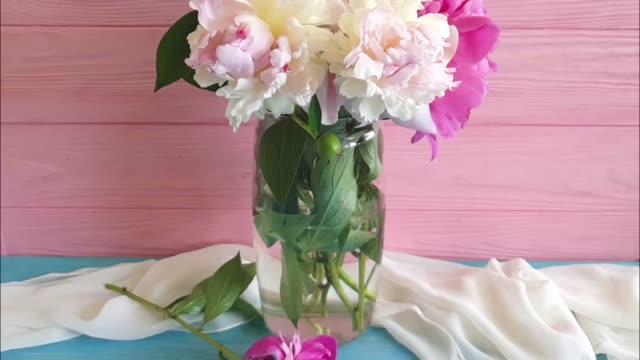 vidéos et rushes de fleur de pivoine dans un vase sur un fond en bois ralenti - composition florale
