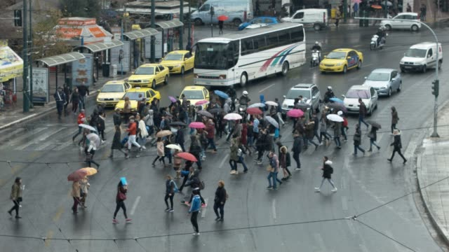 People and cars at traffic lights and crosswalk downtown Athens, Greece, during rain at Syntagma Square video
