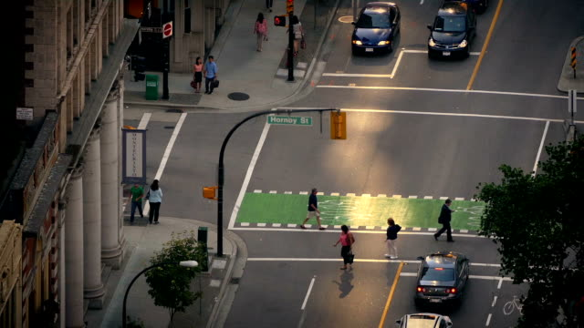 People And Cars Crossing Intersection In Evening Light video