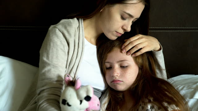 vídeos de stock e filmes b-roll de people and family concept - sad girl with mother sitting on sofa at home.single mom worries about her future.girl missing her father. - mãe solteira