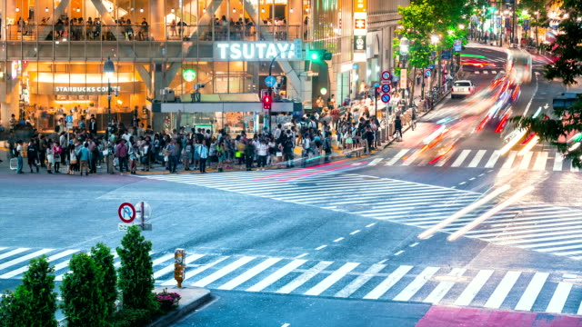 People and vehicles cross the famous Shibuya intersection in Tokyo in time lapse video