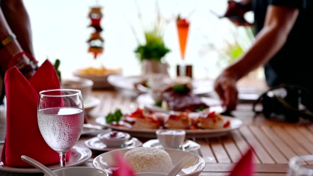 People are arranging variety food on wooden dining table in tropical sea