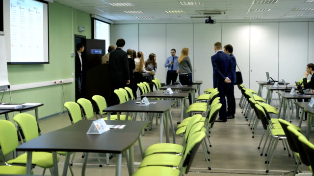 People are coming into a classroom and preparing to business training video