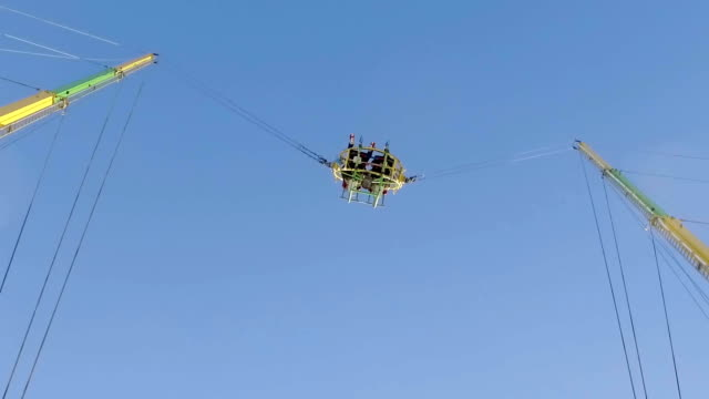 people are having fun in reverse bungee jumping in amusement park, slow motion - bungee jumping video stock e b–roll