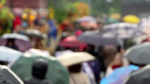 People are holding umbrellas in busy shopping street protecting themselves against rain. Rain starts, people open umbrellas. Real time. People with umbrellas in the rain going to or from work. Blurred bokeh. Naturale background of rainy day on city street video