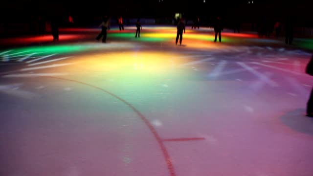 People are in night skating rink with dynamic illumination video