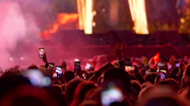 Video People are jumping with their hands up, holding their smartphones and watching a concert. All is illuminated with stage light. 4K