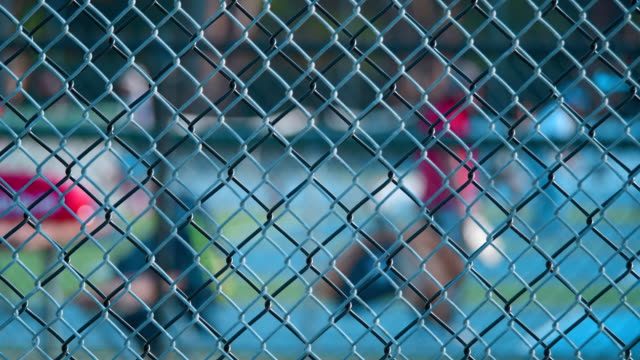 People are playing tennis out of focus behind the fence. video