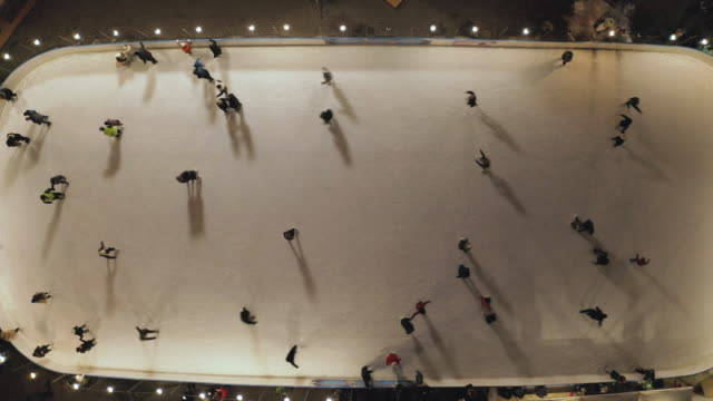 People are skating on ice rink in the evening. Aerial vertical top-down view.
