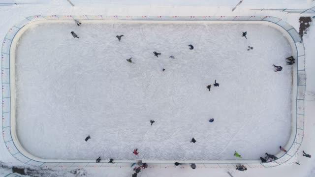 ludzie jeżdżą na łyżwach na lodowisku w słoneczny dzień. powietrzny pionowy widok z góry na dół. ustanowienie strzału. dron unosi się. - łyżwa filmów i materiałów b-roll