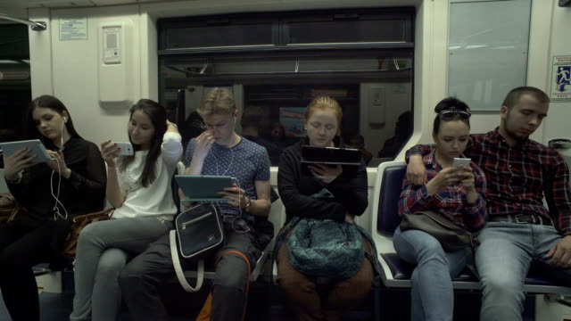 People Are Using Tablets While Riding A Metro Young people reading news online, using app, texting on gadgetsin metro train underground stock videos & royalty-free footage