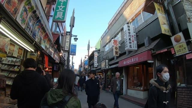 People are walking through Komachi Dori Shopping street in Kamakura, Japan