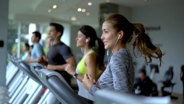 결정 보고 디딜 방 아에서 실행 되는 피트 니스 센터에서 사람들 - 체육관 스톡 비디오 및 b-롤 화면