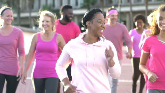 vídeos de stock e filmes b-roll de people at breast cancer awareness event walking, talking - benefits