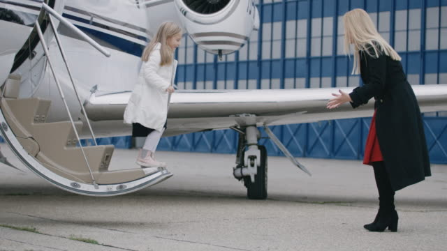 People at the airport Little girl jumping from the stairs of private jet airplane towards her mother. private airplane stock videos & royalty-free footage