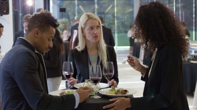 personer på konferensen centrerar en måltid och prata medan de stod vid bordet - affärskonferens bildbanksvideor och videomaterial från bakom kulisserna