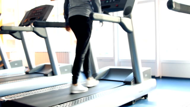 People at the gym exercising. Run on a machine. video