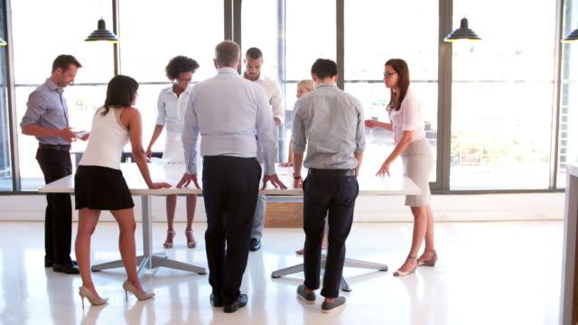 people attending business meeting in modern open plan office - kommunikationssätt bildbanksvideor och videomaterial från bakom kulisserna