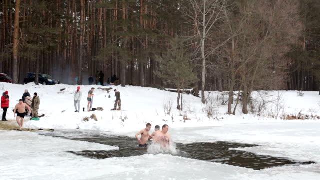 vidéos et rushes de les gens se baignent dans le trou lors de la célébration de l'épiphanie. - baptême