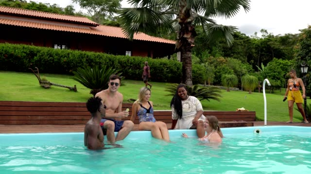 People bathing by the pool in summer People bathing by the pool at the tropical tourist resort pool party stock videos & royalty-free footage