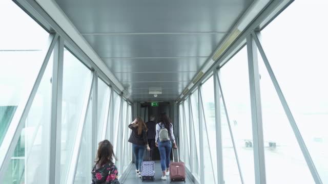 people boarding a plane through a tunnel - wchodzić na pokład filmów i materiałów b-roll