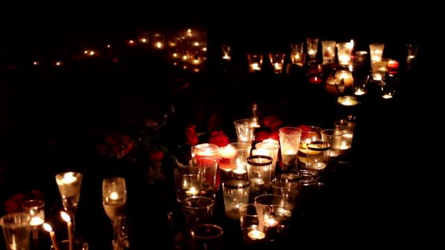 menschen bringen kerzen und blumen in die szene des terroranschlags um die erinnerung an die toten zu ehren. politik, militärische aktionen, terrorismus. menschen trauern - mahnwachen stock-videos und b-roll-filmmaterial