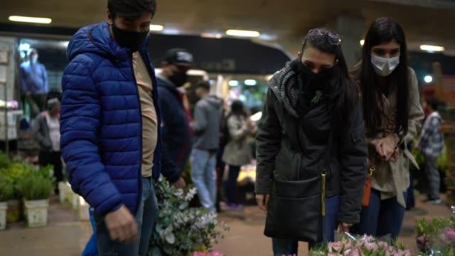 folk köper blommor på nattmarknaden - med ansiktsmask - blomstermarknad bildbanksvideor och videomaterial från bakom kulisserna